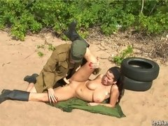 Sand-covered busty soldier trained and straponed